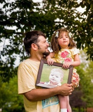 Trinity Lazo, a heart transplant recipient, holding a photograph of Logan, her donor. To read her story, click here.